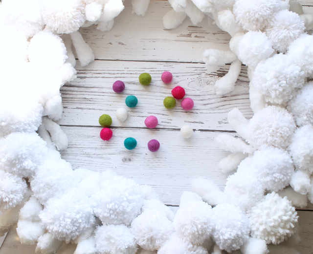 Placing pom poms and gluing on wreath